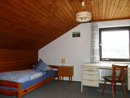 Möbliertes Zimmer mit Waschbeckken und Kochgelegenheit