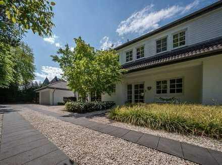 Einseitig angebautes Einfamilienhaus auf großem Gartengrundstück mit altem Baumbestand