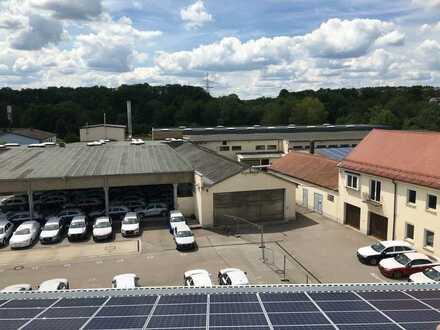 Gewerbeareal mit mehreren Hallen, Bürogebäude großer Freifläche und Photovoltaikanlage