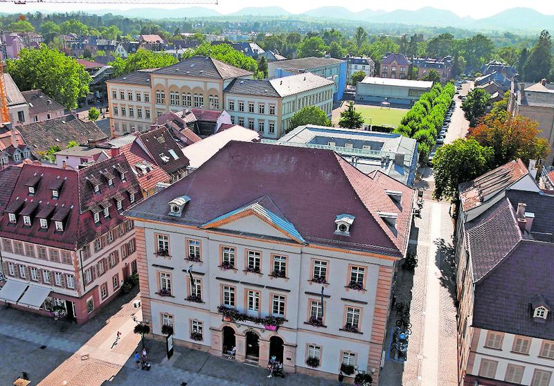 Das Landauer Rathaus, im Hintergrund ein Teil des Rebenmeeres an der Südlichen Weinstraße und Hügel des Pfälzerwaldes. Foto: srä