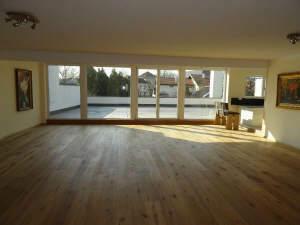 Wohnzimmer mit Glasfront zur Dachterrasse